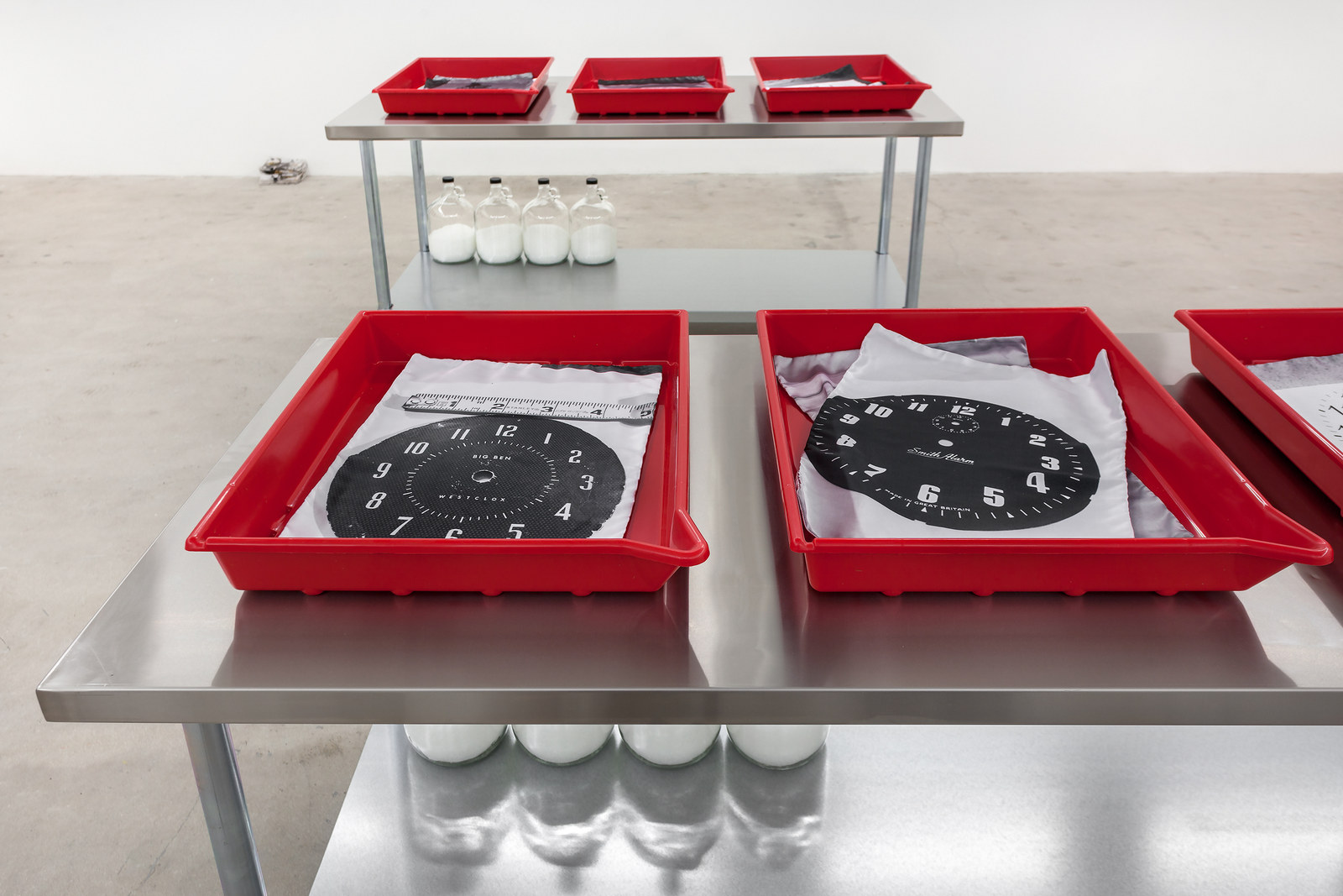 ARH_Untitled Procession (WATCH LIST)_stainless steel table, photo developing trays, inkjet on satin, glass jugs, Epsom salts_37 x 72 x 30_2016_MJ&A